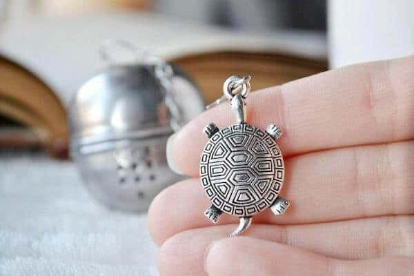 A woman's hand  holds a silver turtle charm attached to a tea ball, which is visible in the background