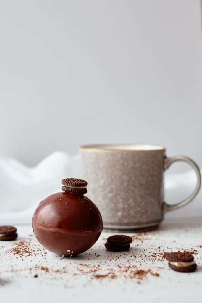 A milk chocolate and Oreo hot chocolate bomb sits on a white counter in front of a mug. There is cocoa and mini oreos scattered around the hot cocoa bomb, and a mini Oreo stuck to the top of it.