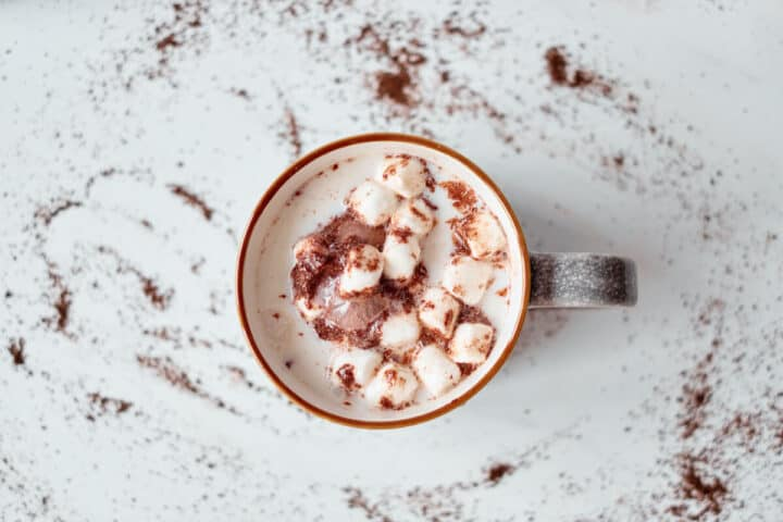Mini marshmallows, hot chocolate mix, and a melting hot chocolate bomb are shown melting in a mug of hot milk.