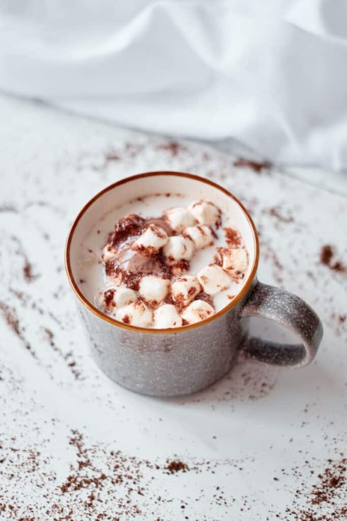 A mug  of hot cocoa made from a hot cocoa bomb. The photo shows a birds-eye view of the mug with mini marshmallows, chocolate, and hot cocoa mix melting into steamed milk.