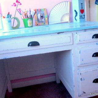 The final photo of a DIY desk makeover project shows a white and blue desk for a girls room, staged with desk accessories