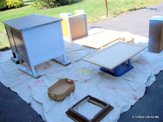 Old furniture sits on a drop cloth and dries after being painted white.