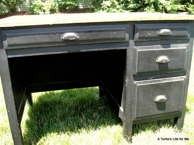 An old wooden desk salvaged from a garage sale sits on grassy lawn. The desk is black and scratched and ripe for a DIY desk makeover.