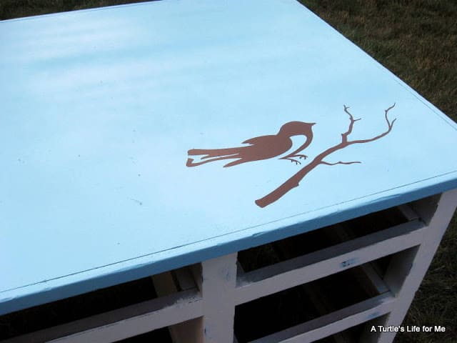 A brown bird on a branch is stencilled on a blue desk top