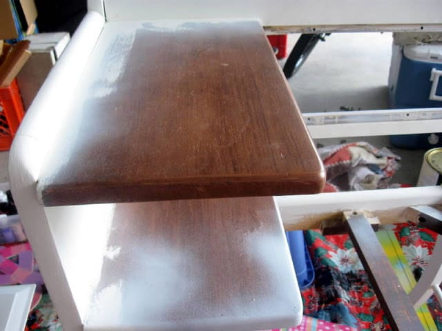 A close up shot showing an old telephone bench being painted white