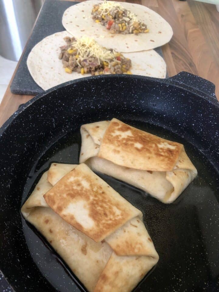 Cooking chimichangas. Frying in oil in a pan.