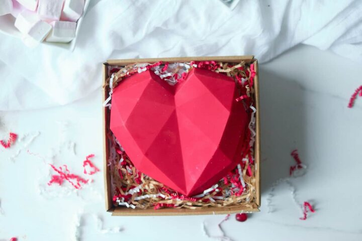 An edible chocolate box made from red candy melts sits in a box on a bed of shredded paper