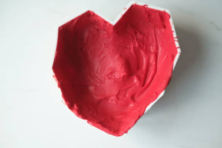 An process shot showing an edible chocolate heart setting in the mold.