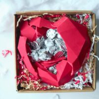 An edible chocolate box is cracked open to reveal wrapped Hershey's Kisses chocolates inside.