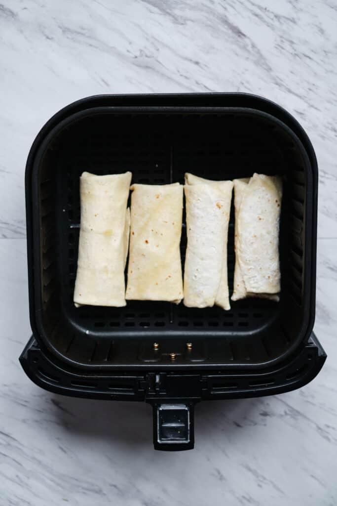 4 frozen burritos lining the basket of an air fryer