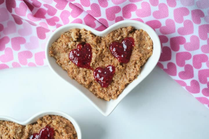 Chocolate oatmeal served in a heart shaped bowl and garnished with red jam hearts
