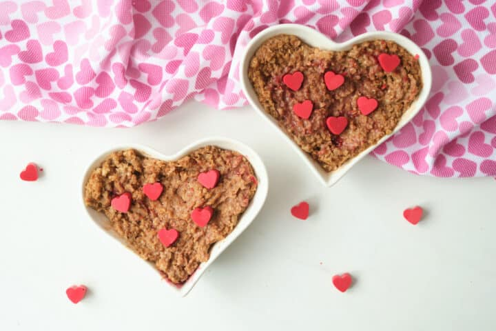 Chocolate oatmeal served in a heart shaped bowl and garnished with red hearts made from melting wafers