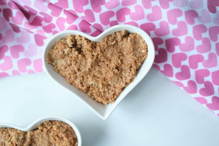 Chocolate oatmeal in a heart shaped bowl for Valentine's Day breakfast, with a heart pattern napkin in the shot