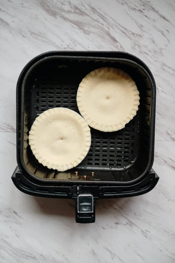 Two small frozen pot pies in an air fryer before cooking