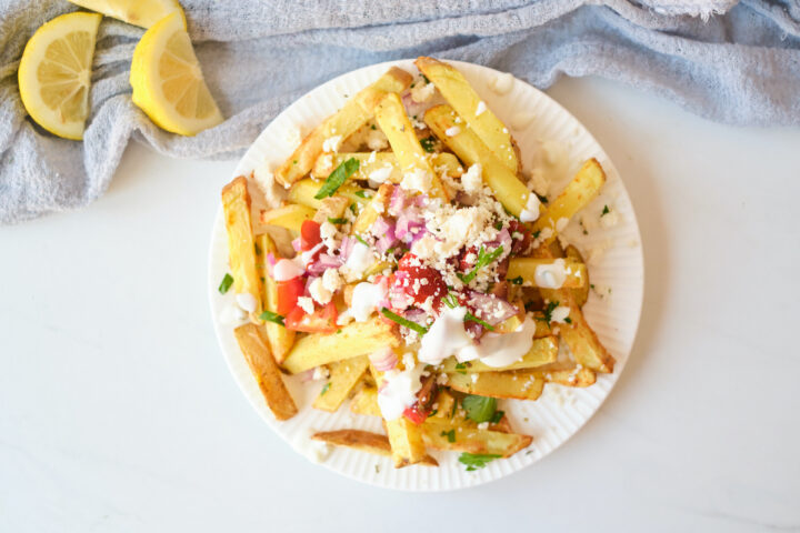 Loaded greek feta fries with feta, tzatziki, parsley, red onion and tomato
