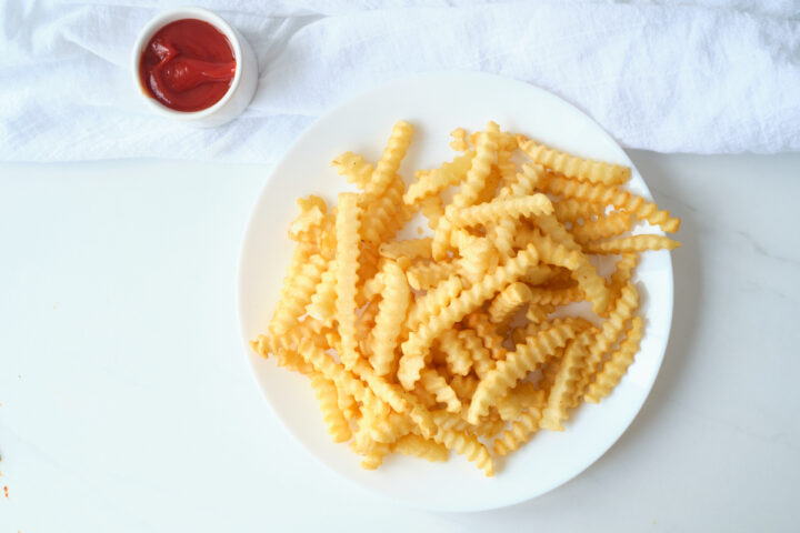 A plate of crinkle cut fries and a small dish of ketchup