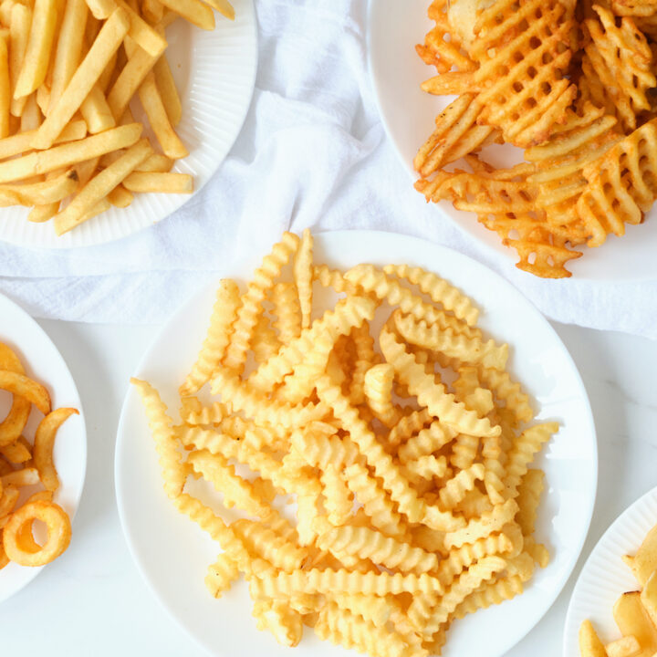 5 plates containing 5 different types of frozen fries after being cooked in an air fryer.