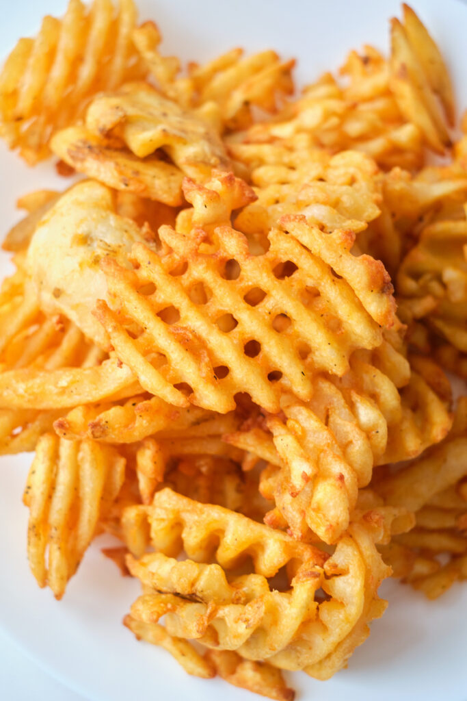 A close up of golden and crispy waffle fries piled on a plate