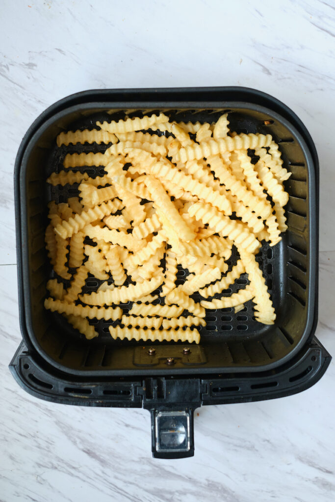 Frozen crinkle cut fries in air fryer basket before cooking