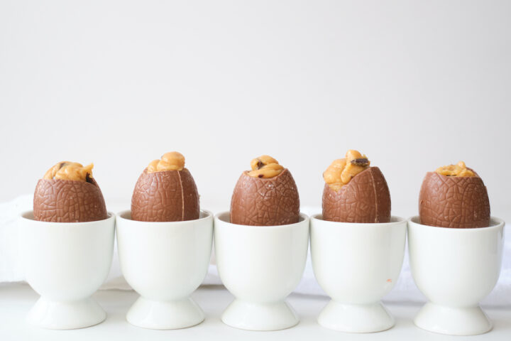 A row of peanut butter filled easter eggs in which egg cups against a white background