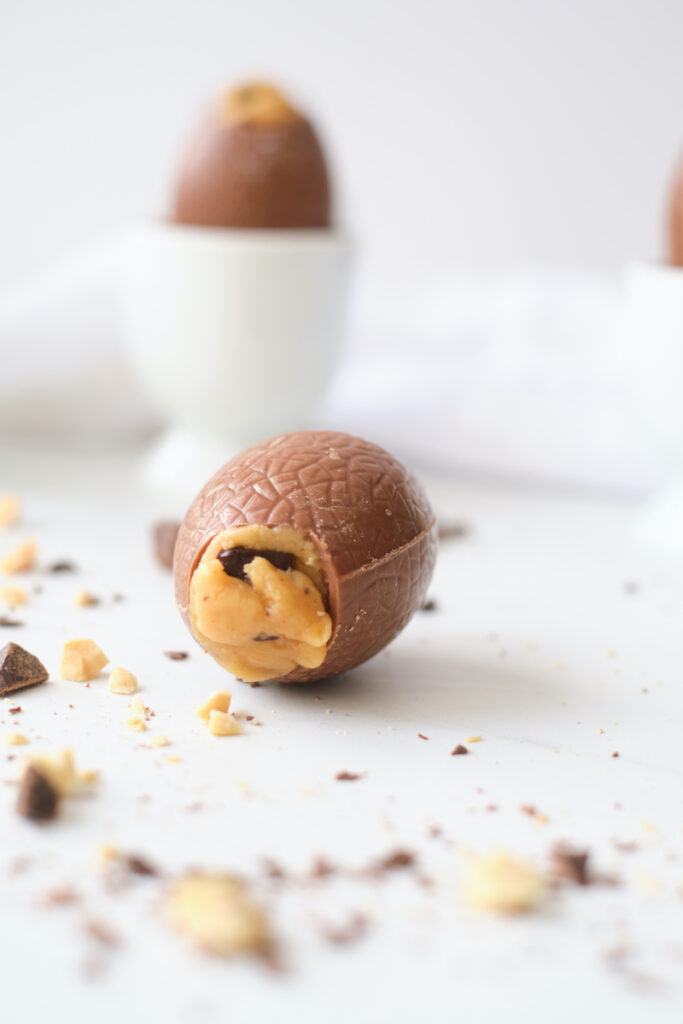 A peanut butter and chocolate chunk filled easter egg lies on its side on a white counter, with peanuts and chocolate chunks strewn around it