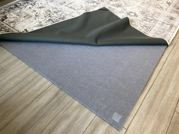 The Ruggable Kamran Hazel rug is pulled back from a thick underpad to show the Ruggable washable layer system as part of a Ruggable review blog post