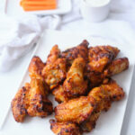 A white dinner plate piled high with buffalo chicken wings, with fresh carrot sticks and dip in the background. The photo shows an after shot for a tutorial about how to cook frozen chicken wings in air fryer.