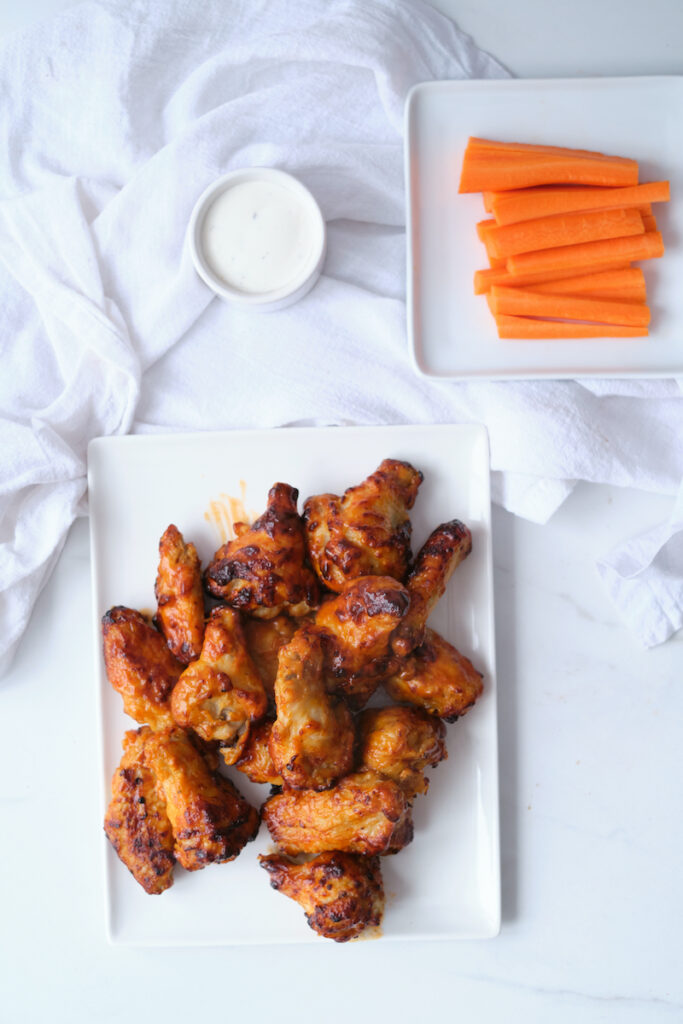 Air fried buffalo chicken wings on a plate with carrot sticks and dip in view
