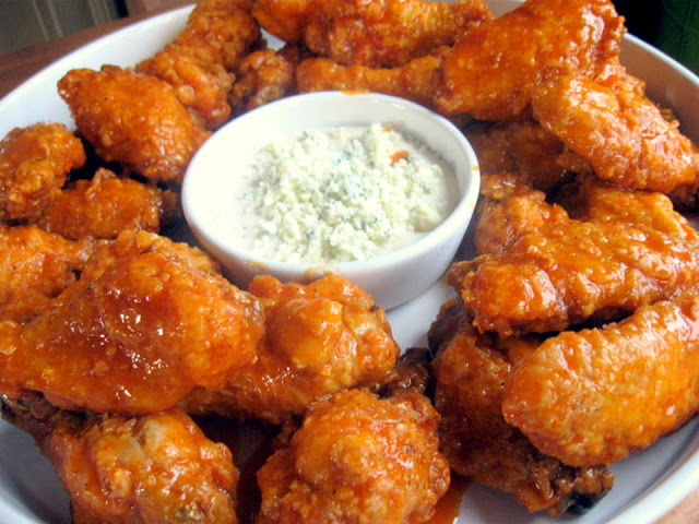 Homemade buffalo chicken wings on a platter, with a dish of blue cheese dip in the center