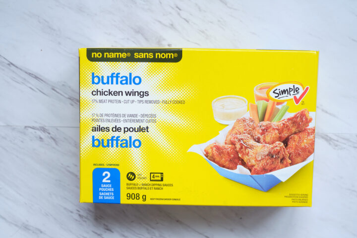A box of no name frozen buffalo chicken wings on a white marble background