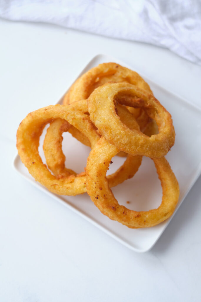 Frozen onion rings after being cooked in an air fryer on a dinner plate