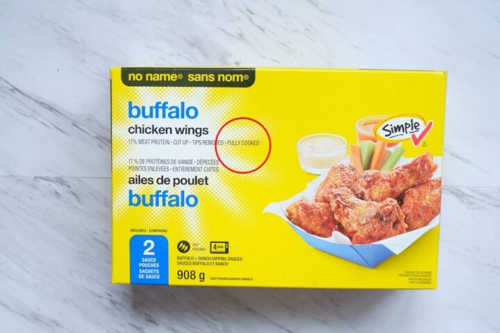 "A box of no name frozen buffalo chicken wings on a white marble background. There is a red outline of a circle on the box to point out the words ""Fully Cooked"""