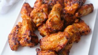 A close up of crispy hot chicken wings on a white plate.