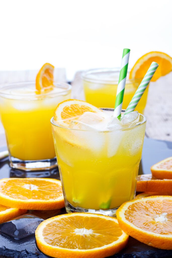 Orange crush cocktails with slices of orange scattered about