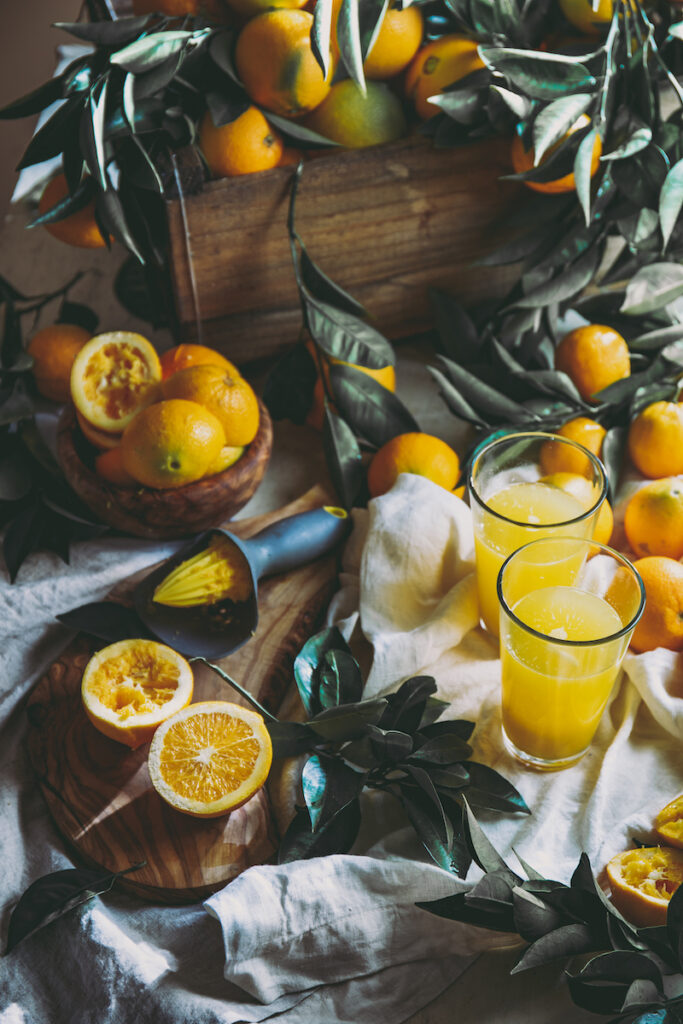 Table with orange juice and box of oranges and orange tree leaves. Some oranges have been juiced and crushed