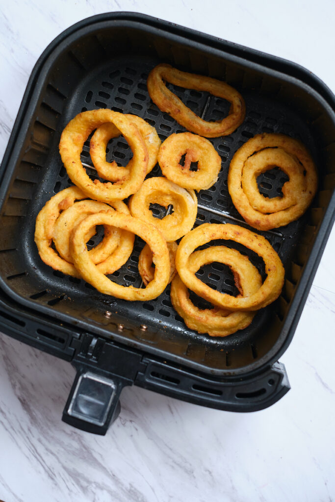 frozen onion rings after being cooked to a golden brown in an air fryer basket