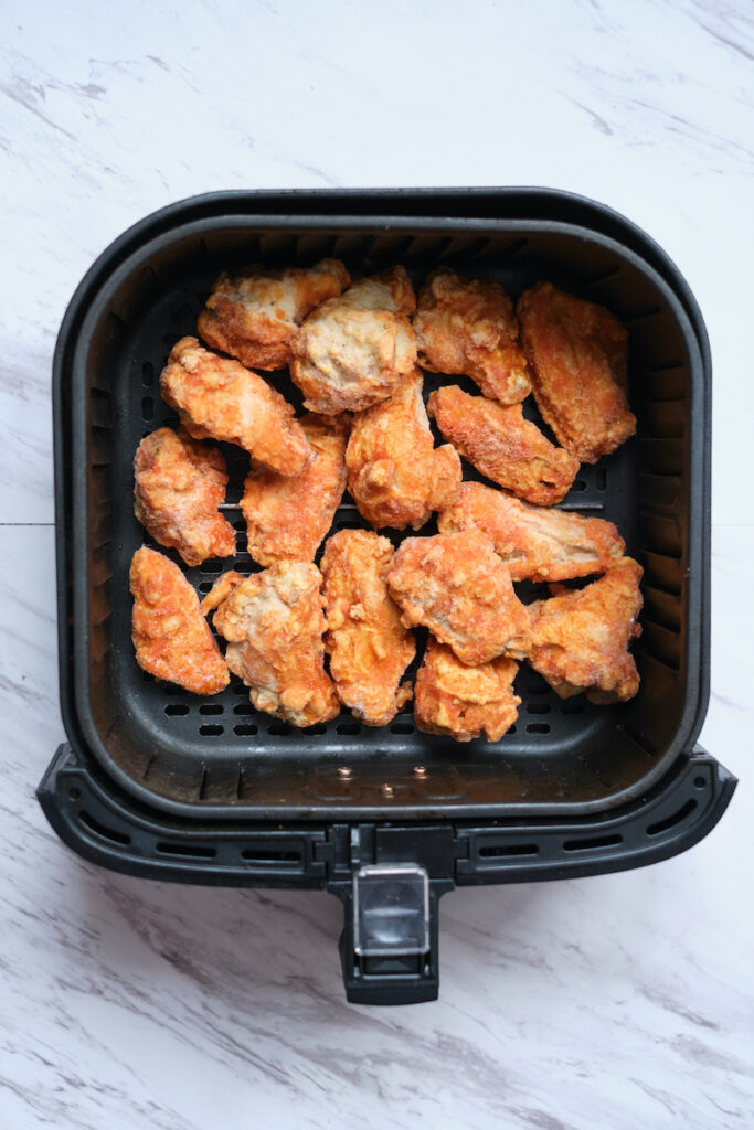 Frozen chicken wings in air fryer basket before cooking