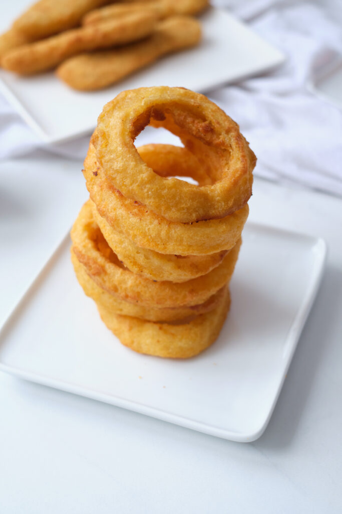 Stack of air fryer onion rings on a white dinner plate.