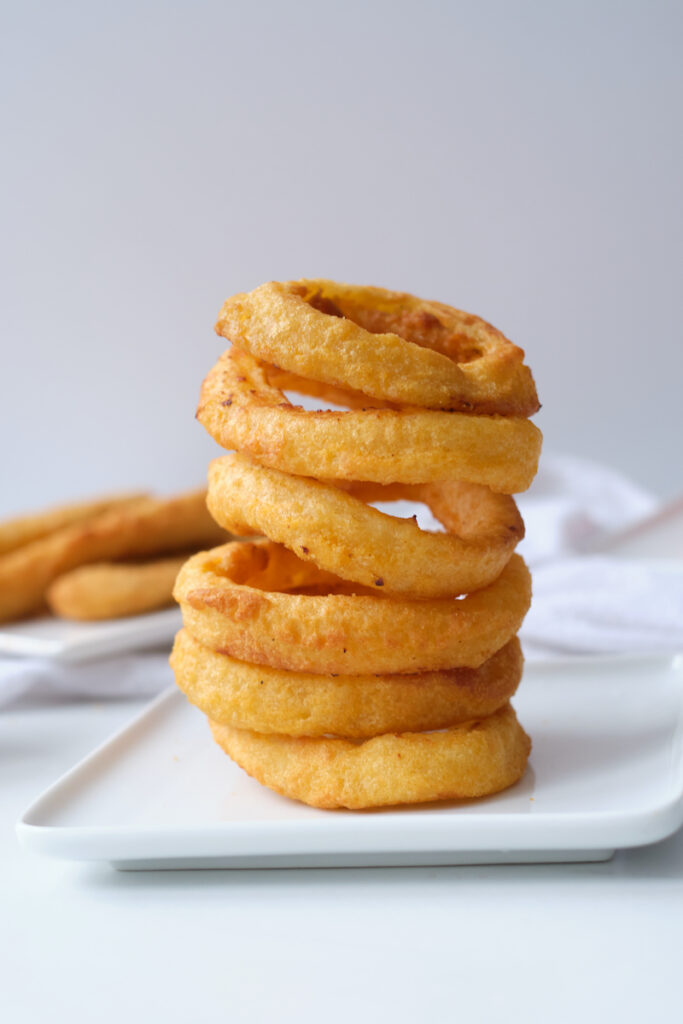 Stack of air fryer onion rings on a white dinner plate with chicken tenders in the background and out of focus