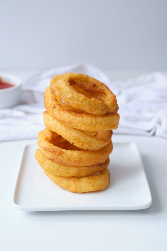Stack of air fryer onion rings on a white dinner plate, with a dipping dish of ketchup partially in view in the background