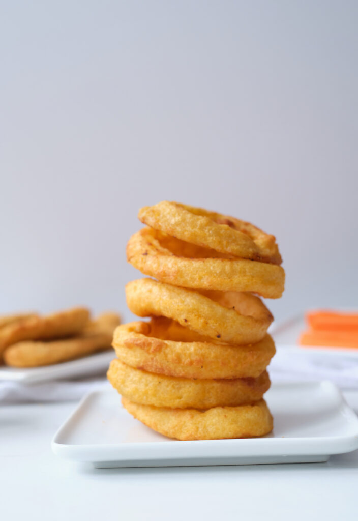 Stack of air fryer onion rings on a white dinner plate, with chicken tenders and carrot sticks in the background out of focus