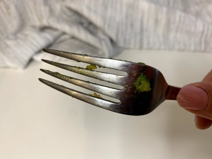 A woman's hand holds a dirty fork with smushed avocado on it before testing different dishwasher detergents to find the best