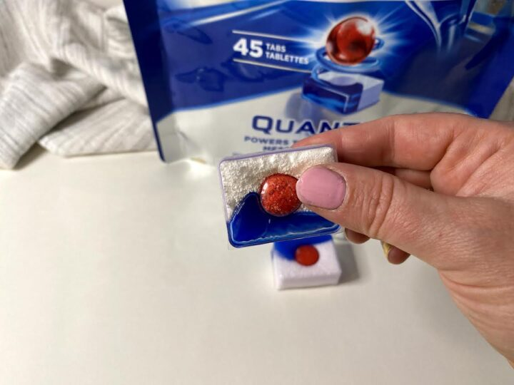 A woman's hand holds a Finish dish detergent pack in the foreground, with a partial view of the package in the background