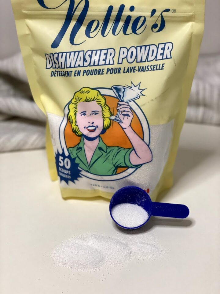 A bag of Nellie's eco friendly dishwasher powder detergent on a white counter, with some of the powder spilled in front