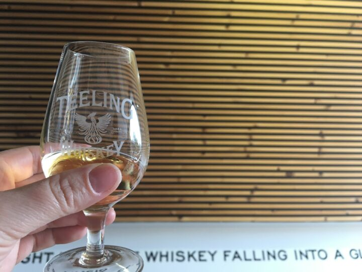 A woman's hand holds a small taster of Teeling Irish Whiskey in a branded glass against an interested wood wall