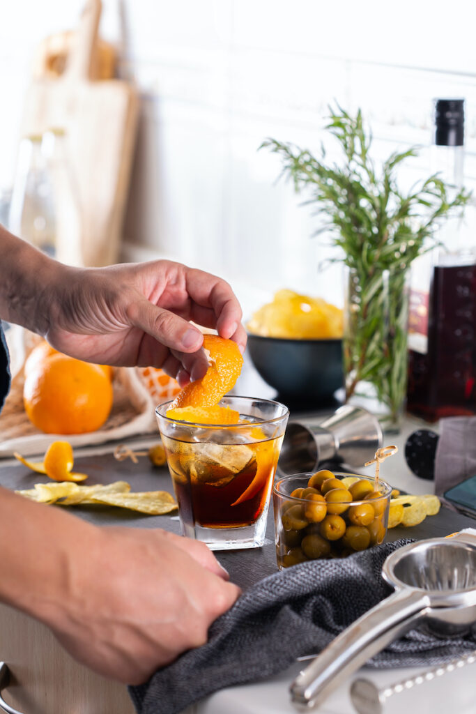 Mixologist making vermouth cocktail while at home using some home bar essentials such as proper glasses and garnishes