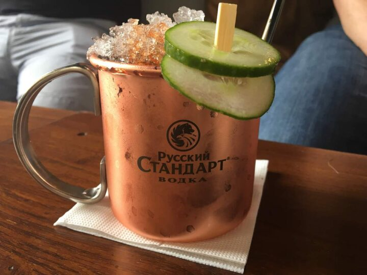 Close up of a moscow mule in a frosty copper mug piled high with crushed ice and garnished with cucumber